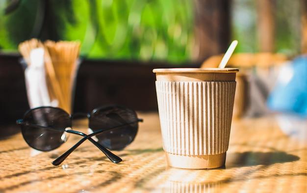 木製スターラー、サングラスの近くのカフェのテーブルのホルダー付き使い捨て紙コーヒーカップ。環境に優しいライフスタイル Premium写真