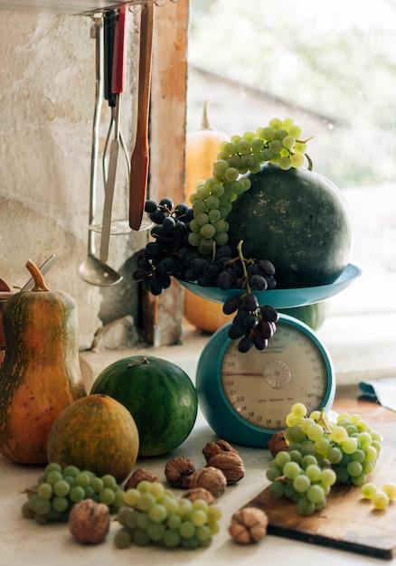 カボチャ、クルミ、メロン、スイカ、ブドウのスケールと木製の白いテーブルの上の秋の静物。 Premium写真