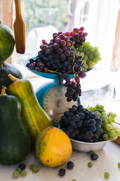 Осенний натюрморт с тыквы, дыни, арбуз, виноград в масштабе и в металлическую чашу на деревянный белый стол. концепция осеннего урожая. Premium Фотографии