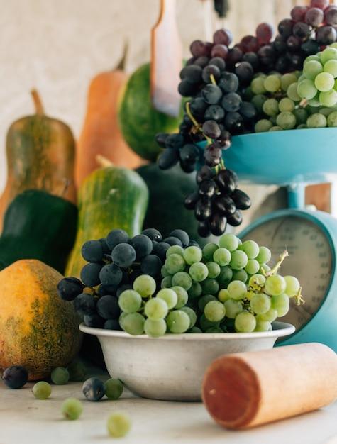 カボチャ、メロン、スイカ、スケールで、木製の白いテーブルの上の金属製のボウルのブドウの秋の静物。秋の収穫のコンセプト。 Premium写真