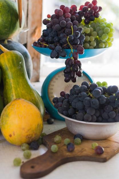 カボチャ、およびスケールと木製の白いテーブルの上の金属製のボウルにブドウの秋の静物。秋の収穫のコンセプト。 Premium写真
