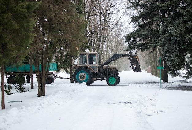 植物園の冬のトレーラー付きトラクターは、雪と枝から道路をきれいにします。 Premium写真