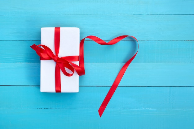 Подарок в белой упаковке с красной лентой Premium Фотографии