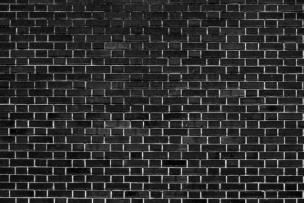 濃い黒レンガの壁は背景画像として粗い表面を有する。 Premium写真