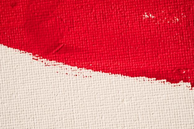 白いキャンバスの背景にテクスチャの赤い色の塗料を閉じる Premium写真