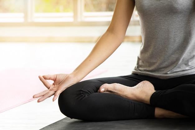 アジアの女性は、ヨガ、独立した概念、女性の幸福、落ち着いた白い部屋の背景を練習しながら瞑想します。 Premium写真
