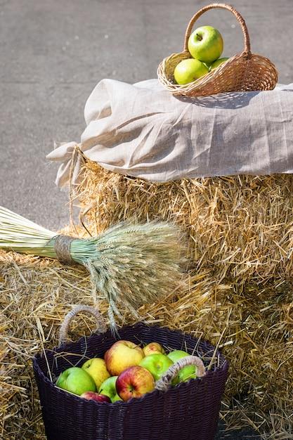 Головки зерна и яблоки в корзинах. сбор урожая на стоге сена Premium Фотографии