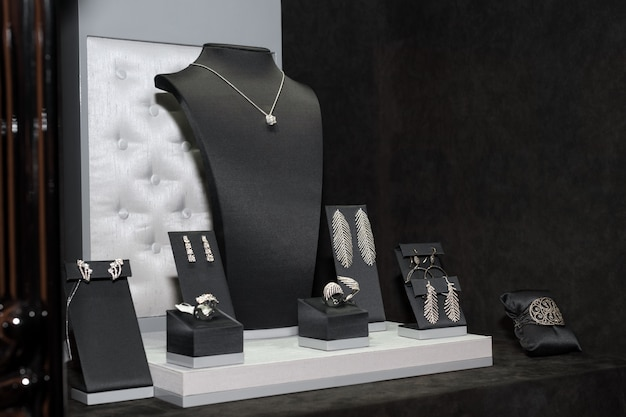 店の窓にあるさまざまなジュエリー。リング、ブレスレット、イヤリング、ネックレス、スタンド販売。 Premium写真