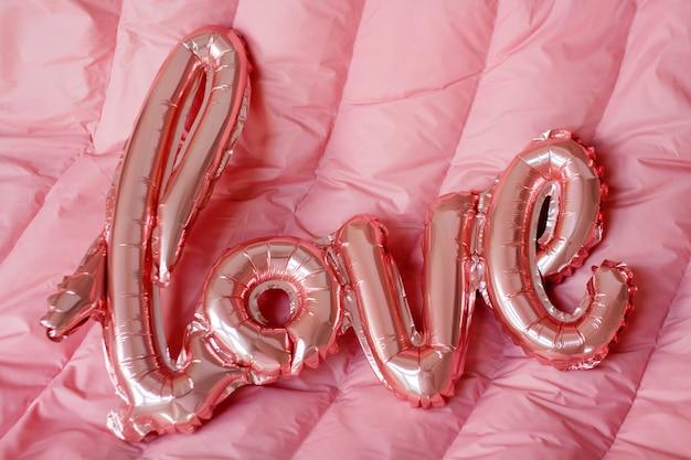 Полюбите слово от розового раздувного воздушного шара на розовой предпосылке. концепция романтики, день святого валентина. любовный воздушный шар из розового золота Premium Фотографии