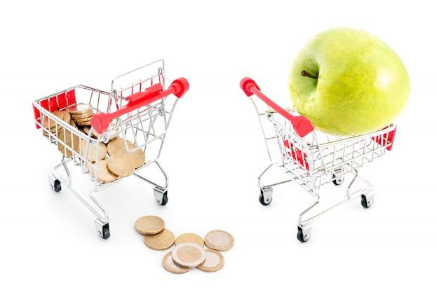 それから白い背景と青リンゴに落ちるユーロ硬貨のショッピングカート。販売、豊富さ、収穫、スーパーマーケットでのショッピング、販売、キャッシュバックのテーマ。 Premium写真