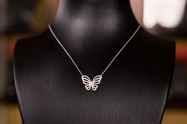 Колье из белого золота с бриллиантами на подставке в модном ювелирном бутике. черная подставка под шею с роскошными украшениями, женскими аксессуарами в витрине. Premium Фотографии