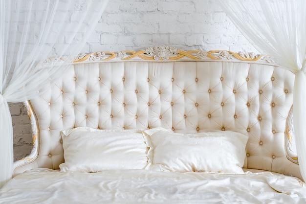 柔らかな明るい色の寝室。エレガントでクラシックなベッドルームの大きな快適なダブルベッド。ゴールドのインテリアデザインと豪華なエレガントな白。 Premium写真