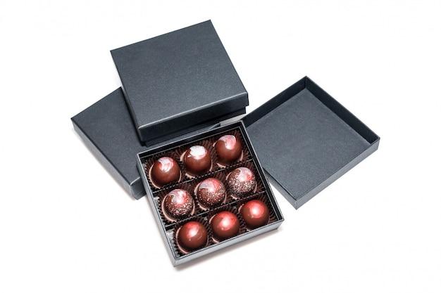 白い表面に分離されたギフトボックスのチョコレート菓子。ギフトボックスに入ったチョコレート菓子の詰め合わせ。カラフルなチョコレートボンボンのセットです。 Premium写真