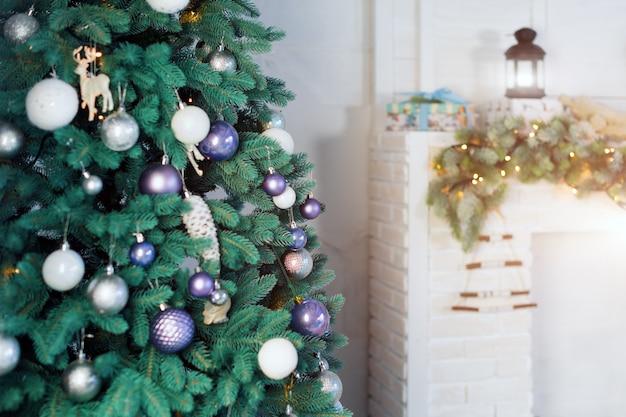 暖炉のそばのクリスマスツリーが飾られた美しい休日の部屋。 Premium写真