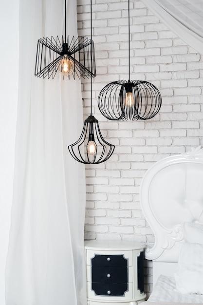Черные лампы в светлый интерьер спальни. три современные черные лампы висят Premium Фотографии