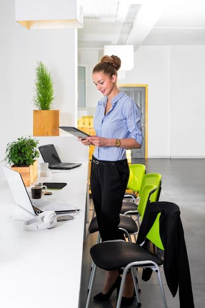 タスクのリストとタブレットを保持している近代的な明るいオフィスで若い実業家。事務作業のビジネスコンセプトです。 Premium写真