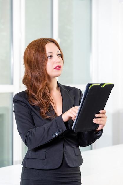 タスクのリストとタブレットを保持している近代的な明るいオフィスで若い実業家 Premium写真