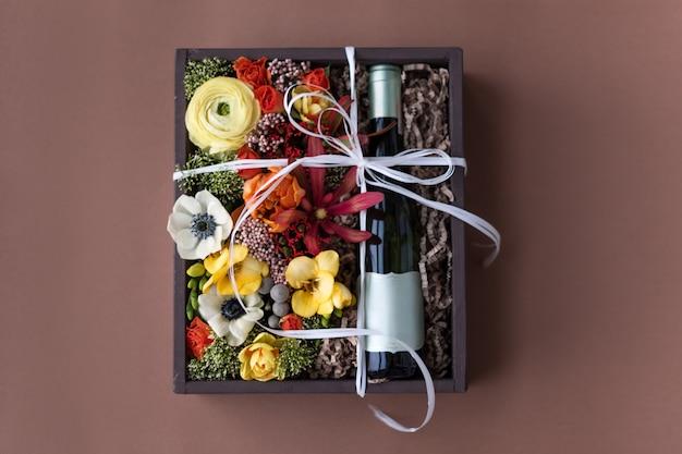 古い木製の素朴なボックスに白ワインのボトルと花の花束 Premium写真