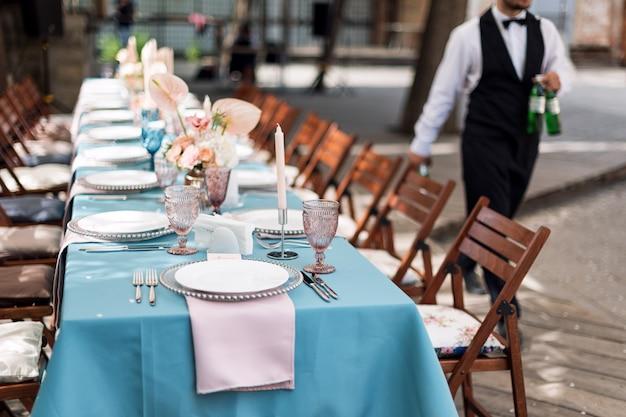 休日や結婚式の夕食のための花のテーブルデコレーション。屋外レストランでの休日の結婚披露宴のテーブル。 Premium写真