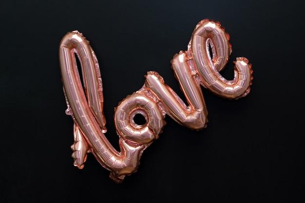 Любовное слово от розового надувного шара на черном, изолированного на черном Premium Фотографии