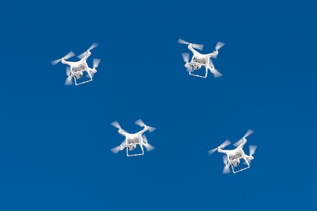 何十ものドローンが青空に群がります。クアッドコプターの無人偵察機とデジタルカメラを空中都市。 Premium写真