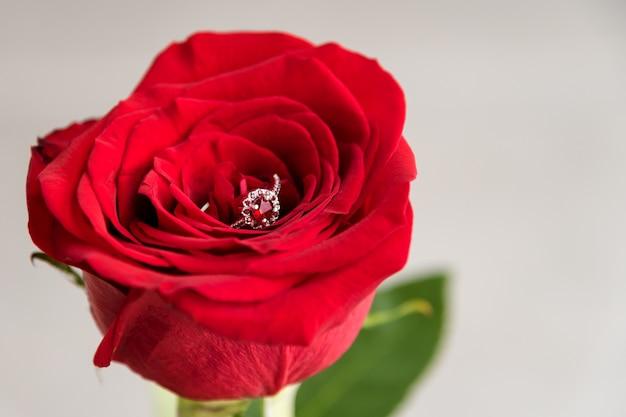 Сверкающее обручальное кольцо внутри красной розы. Premium Фотографии