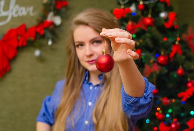 Портрет девушки с ярко-красными губами, светлыми длинными волосами молодая девушка в синей мужской рубашке. держа перед ним рождественский бал есть шар Premium Фотографии
