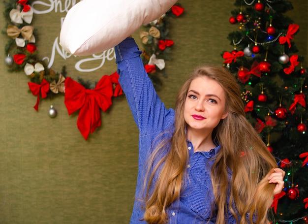 Портрет девушки с ярко-красными губами, длинными светлыми волосами молодая девушка в синей рубашке с белой подушкой в руках Premium Фотографии