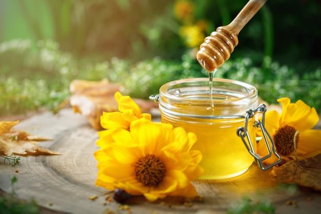 Свежий цветочный мед на деревянном столе. выборочный фокус. Premium Фотографии