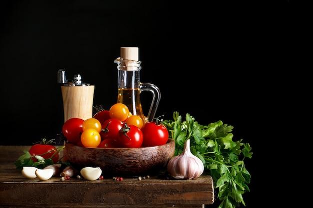 木の板にトマト、ニンニク、オリーブオイルのある静物。 Premium写真