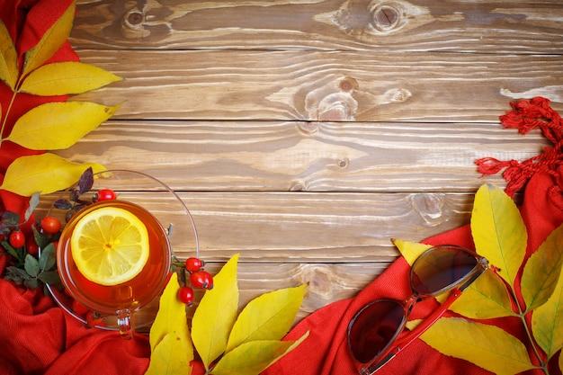 秋の紅葉、果実、新鮮なお茶で飾られたテーブル。秋。秋の背景。 Premium写真