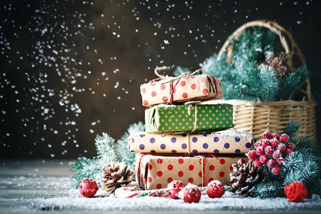 クリスマスのおもちゃと木製の背景にクリスマスプレゼント付きバスケット Premium写真