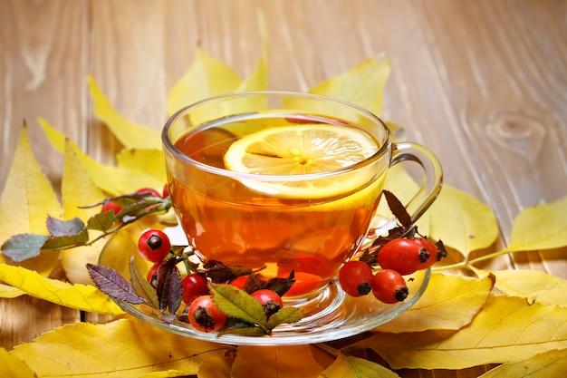 Стол украшен осенними листьями, ягодами и свежим чаем Premium Фотографии