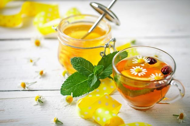 健康的なお茶のカップ、蜂蜜と花の瓶。セレクティブフォーカス Premium写真