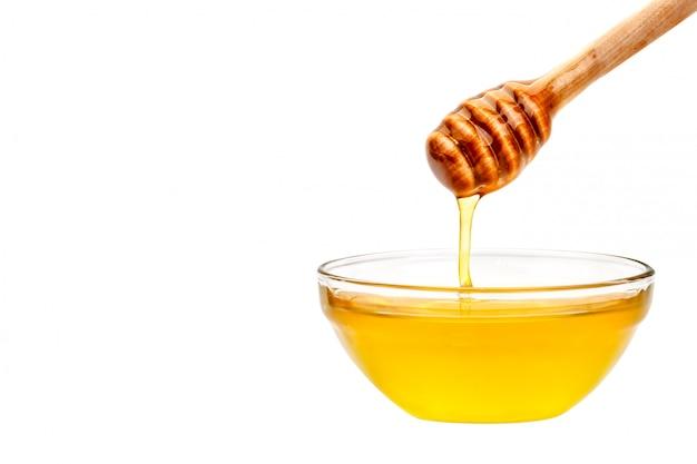スプーンから滴り落ちる新鮮な蜂蜜。白い背景の上 Premium写真