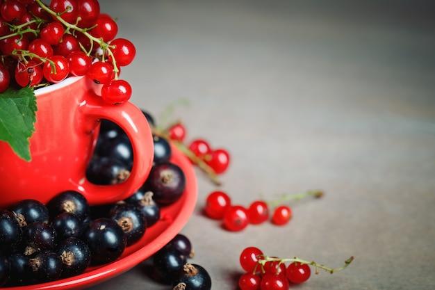 木製のテーブルに熟した赤と黒スグリ。 Premium写真