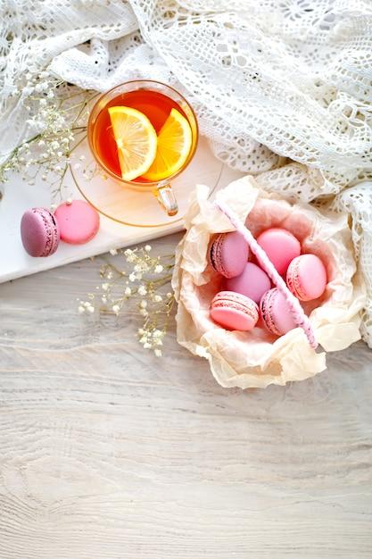 Чай с лимоном, полевыми цветами и макаронами на белом деревянном столе Premium Фотографии