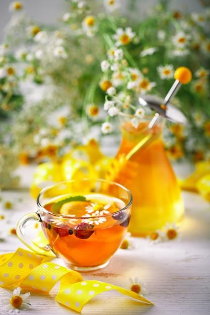 Здоровая чашка чая, банка меда и цветов. выборочный фокус. Premium Фотографии