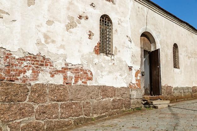 Потертый фасад здания с открытой дверью и окном. историческое старое здание. Premium Фотографии