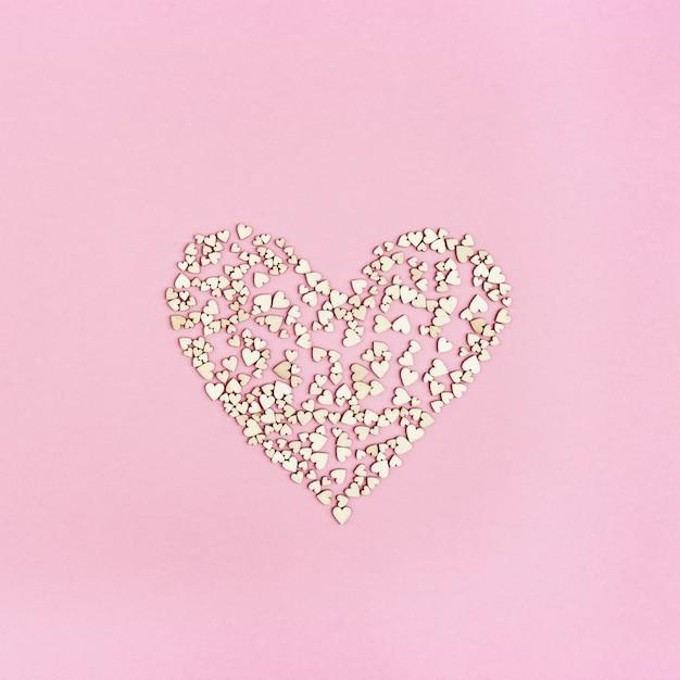 Большое сердце наполнено любовью. много маленьких деревянных сердечек. открытка или приглашение на свадьбу или валентина. Premium Фотографии