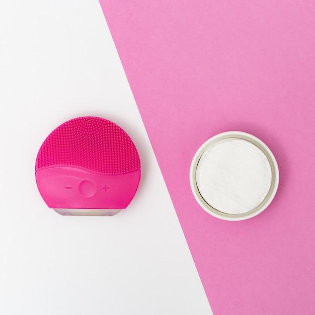 女性の美しさと衛生製品、赤い電動フェイスブラシ、白とピンクの紙の背景に綿のパッド。美顔術。フラットレイアウトスタイル。上面図。 Premium写真