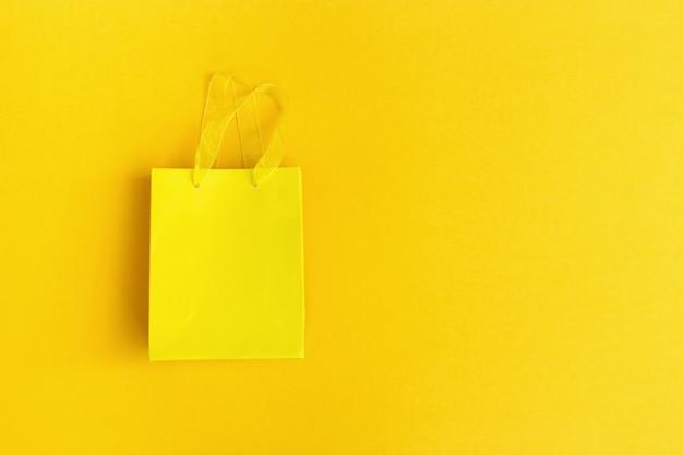 黄色の紙の背景に黄色のギフトバッグ Premium写真