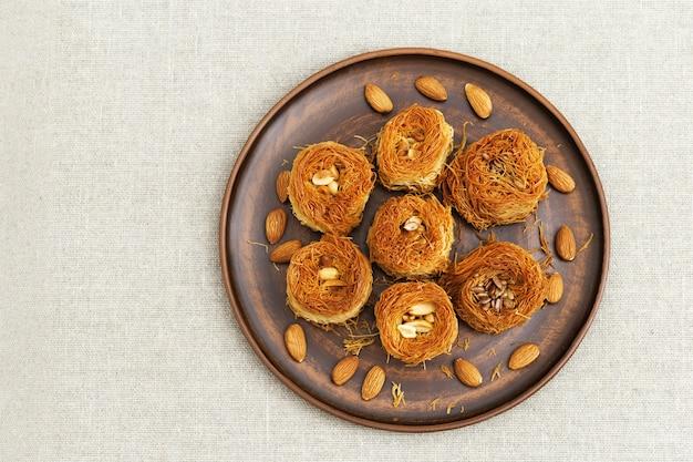 伝統的な中東の甘い鳥の巣、蜂蜜のシロップとテキスタイルテーブルリスのプレート上のナッツ。薄い生地のフィロからのおいしい蜂蜜のデザート。上面図。 Premium写真