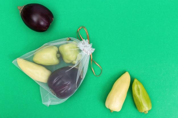 Зеленый перец и баклажаны в многоразовых эко мешках на фоне зеленой книги. свежие овощи в пакетиках из прозрачного текстиля для хранения продуктов. пластиковая бесплатная концепция. квартира лежала. вид сверху. Premium Фотографии