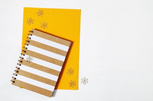 Весенний закрытый блокнот с золотой обложкой и фигурными металлическими зажимами на желтых бумажных листах. обратно в школу концепции. вид сверху. Premium Фотографии