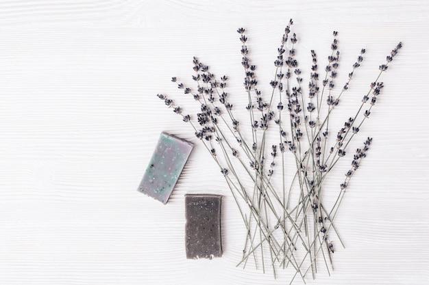 天然オーガニック食材を使った手作り石鹸バー、コピースペース付きの白い木のテーブルにラベンダーの花を乾燥させました。アロマセラピー、美容スパ。上面図。 Premium写真