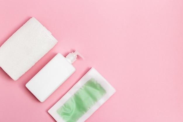 脱毛、ボディモイスチャライザー、ピンクの白いコットンタオル用の使い捨てワックスストリップのセット Premium写真