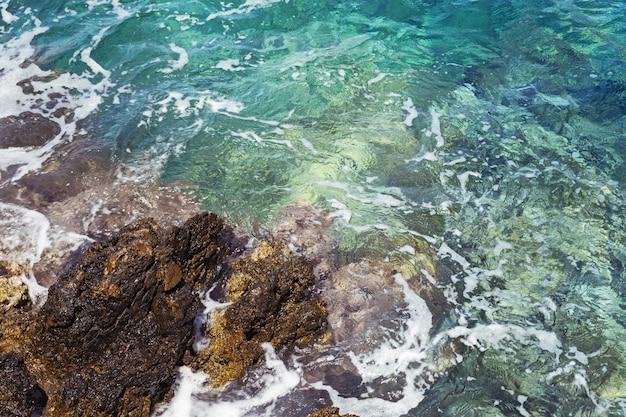 岩とターコイズブルーの海水。 Premium写真
