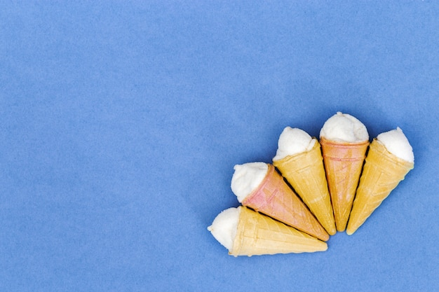 コピースペースを持つ小さなアイスクリームコーン紙の背景。上からの眺め。夏の背景。ミニマリズムのスタイル。 Premium写真