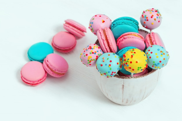 Красочные сладкие миндальное печенье и торт выскакивают в миску на деревянных белых Premium Фотографии